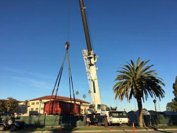 Mobile crane lifting a dumpster out of a jobsite